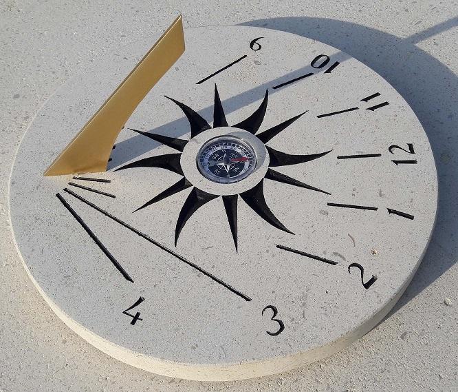 Cadran solaire en pierre de Bourgogne portatif. Boussole au centre avec une correction par rapport au nord géographique. Peinture noire la gravure du soleil et des heures.
