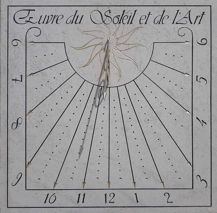 Cadran solaire en pierre de Bourgogne, avec devise Oeuvre du soleil et de l'art. Un soleil doré au centre du style.