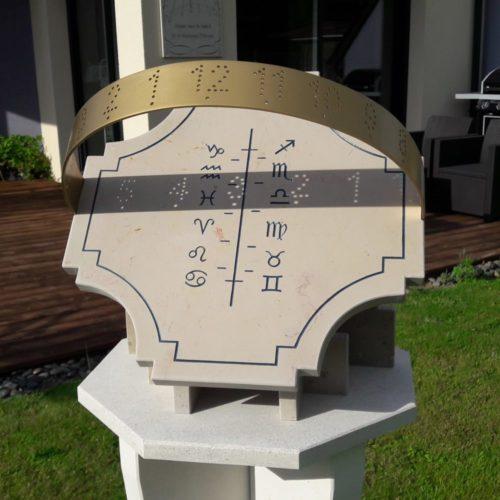 Cadran solaire en pierre de Bourgogne. L'heure est indiqué au passage des chiffres lumineux sur l'axe, elle informe aussi du signe astrologique.