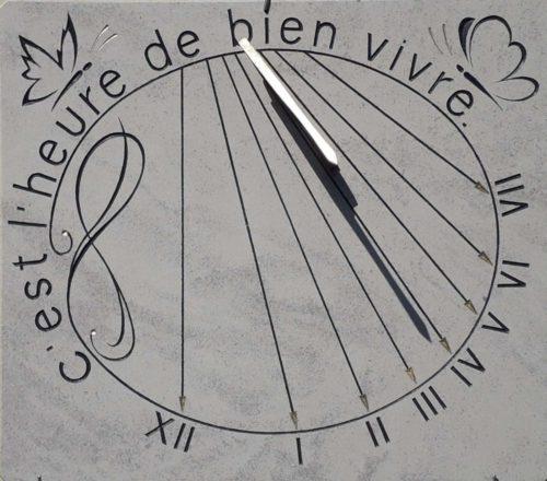 Cadran Solaire en pierre de Bourgogne, avec décoration de papillon et devise, c'est l'heure de bien vivre. Chiffre romain et style en forme de flèche plaqué à la feuille d'or.