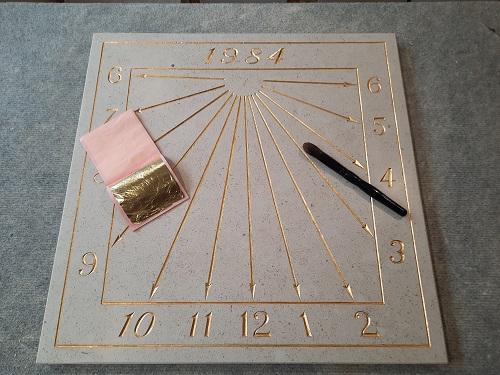 Pose de la feuille d'or sur la gravure du cadran solaire