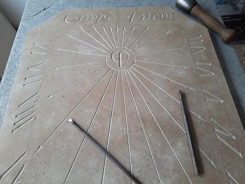 Réalisation d'un cadran solaire en pierre de Bourgogne. Tout le cadran solaire est en proportion avec le nombre d'or. Gravure à la main et pose de la feuille d'or.