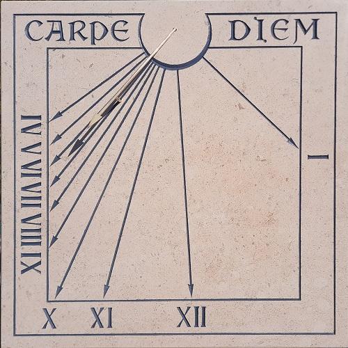 Réalisation d'un cadran solaire en pierre par un artisan cadranier. Gravure des heures en chiffre romain et de la devise Carpe-diem.